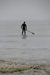 Cet homme qui semble marcher sur les eaux est un rameur pratiquant le stand-up paddle.