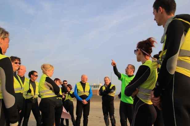 """Les débutants suivent un entretien sur la plage : rappels de """"pourquoi on est là"""" ; bons gestes pour évoluer le plus simplement possible dans l'élément marin ; la sécurité de tous (grâce à la bienveillance de chacun)..."""