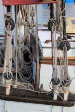 """On voit très bien les caps de mouton, pièces en bois percées permettant de tendre les haubans, cordages servant à soutenir le mât. On appelle ces haubans les manoeuvres dormantes, à savoir les cordages qui ne sont pas utilisés pour les manoeuvres des voiles qu'on dit """"courantes""""."""