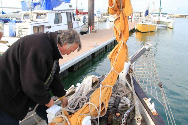 """Le bateau s'apprête à quitter le quai. L'espar (cette flèche de bois dépassant le bateau à la proue) est baissé """"bout devant"""". Les gardes permettant au bateau de rester parallèle au quai sont également larguées. La voile orange que l'on voit ici est encore transfilée (maintenue serrée dans un cordage). C'est une des deux """"voiles d'avant"""" (les voiles situées devant le mât). Cette voile-ci s'appelle la """"trinquette""""."""