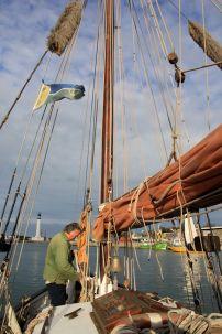 """Le bateau quitte le port de plaisance au moteur, """"bout au vent"""" (face au vent). Luc en profite pour enrouler les cordages en vue de désencombrer le pont. Leur multitude à bord rendrait vite la circulation périlleuse et incompatible avec la nécessité d'effectuer les manoeuvres rapidement."""