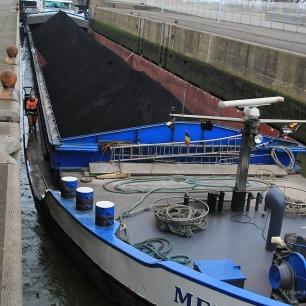 Les péniches fréquentant l'écluse peuvent avoir jusque 115 mètres de longueur. Cette péniche a chargé du charbon au quai minéralier. Une autre vient charger les silos de blé pour le Maghreb ou l'Egypte dans la majorité des cas, voire la Chine. Le tirant d'eau du principal port céréalier français, le port de Rouen, ne permet pas de remplir les navires. On n' y charge environ que 50 000 tonnes. Ceux-ci viennent alors compléter leur chargement à Dunkerque (pour 15 à 20 000 T.)... Mais les fameux bateaux Panamax de 225 mètres viennent de plus en plus se remplir en totalité à Dunkerque... Rouen est plus proche de la Beauce... mais la Seine n'est profonde que de 10 mètres...