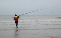 La ligne de Céline est prête. Céline avance dans la mer pour gagner de précieux mètres avant de lancer .