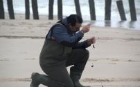 Antoine procède au eschage de sa ligne. Autrement dit, il fixe sur celle-ci des appâts, en l'occurence, des arénicoles, sortes de gros vers cachés dans le sable et qu'on ramasse à marée basse avec une pompe spéciale.